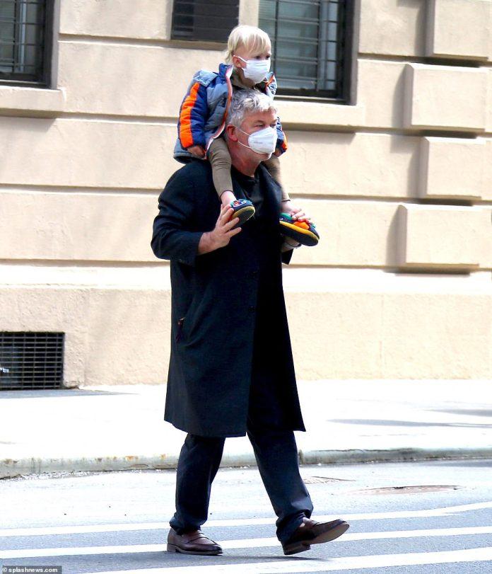 Sobre los hombros de papá: Alec, de 63 años, fue fotografiado con su hijo Alejandro David, de dos, descansando sobre él mientras paseaba por la ciudad.