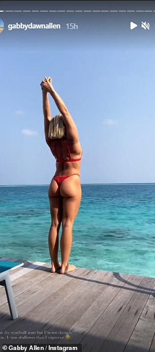 Flaunt:The fitness fanatic stretched her arms into the air before smoothly diving into the water