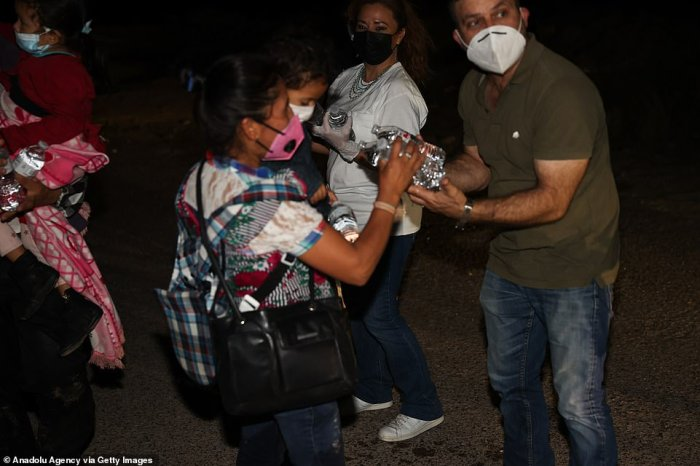 Water bottles are passed out to migrants after they crossed the Rio Grande River Wednesday night