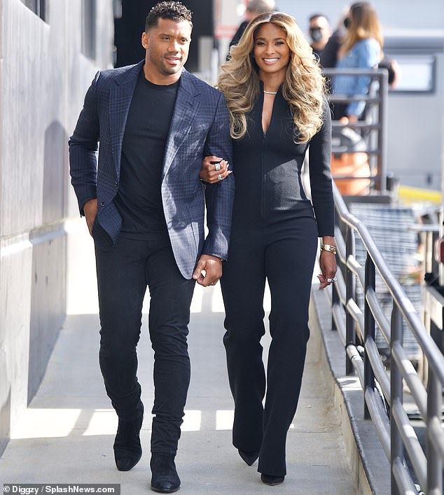 Off they go:The smoldering 32-year-old football player was chic to the hilt in a navy checked blazer with shoulder pads over a basic black look