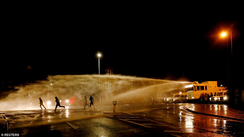 The PSNI use a water cannon on the Springfield road, during further unrest in Belfast tonight