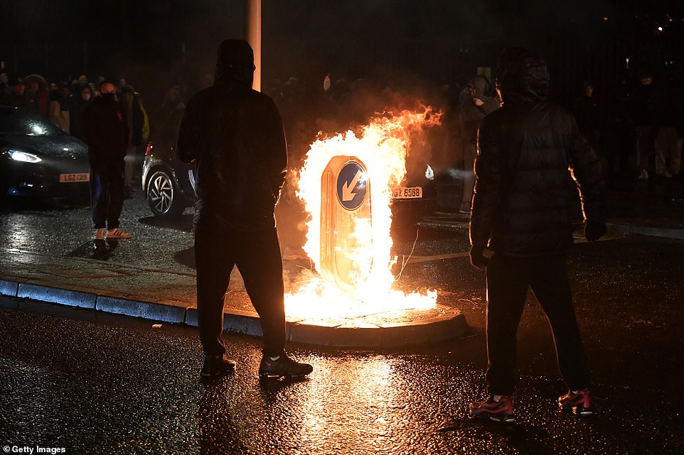 People watch a traffic sign burn as Nationalists attack police on Springfield Road near the Peace Wall