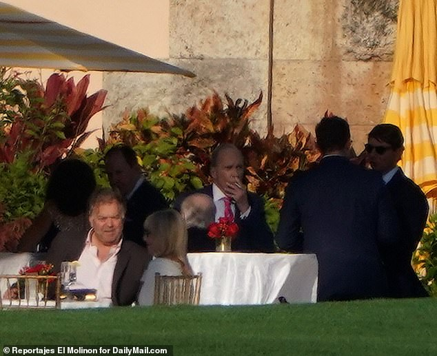 Larry Kudlow, center, is seen smoking a cigarette at Mar-a-Lago during a party for the Conservative Partner Institute on Thursday