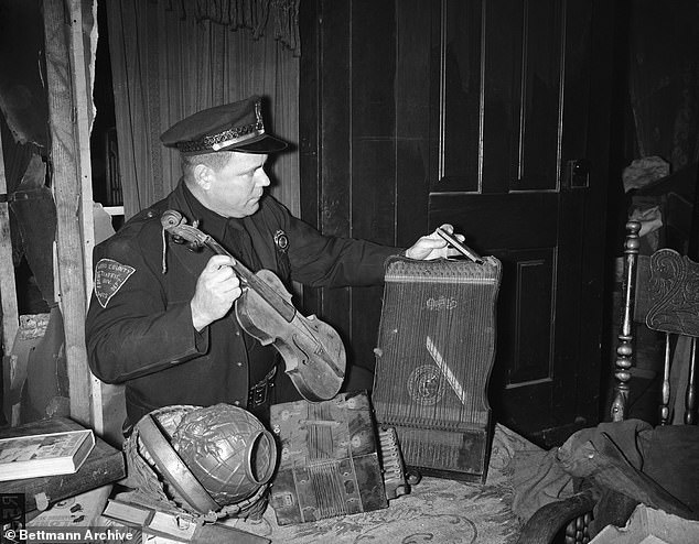 Trooper Dave Sharkey looks over some of the musical instruments found in the home of bachelor farmer Ed Gein