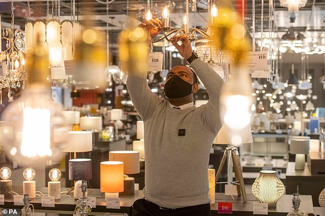 A staff member cleans light fittings at the John Lewis store in White City ahead of it reopening at the start of next week