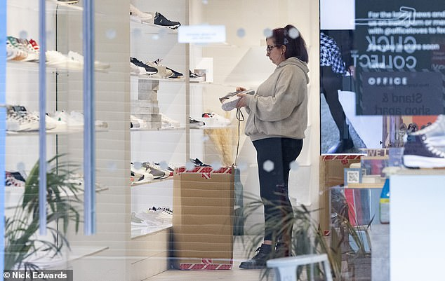 A worker at Office laces up a shoe on Oxford Street in London yesterday as shops prepare for the big reopening on Monday