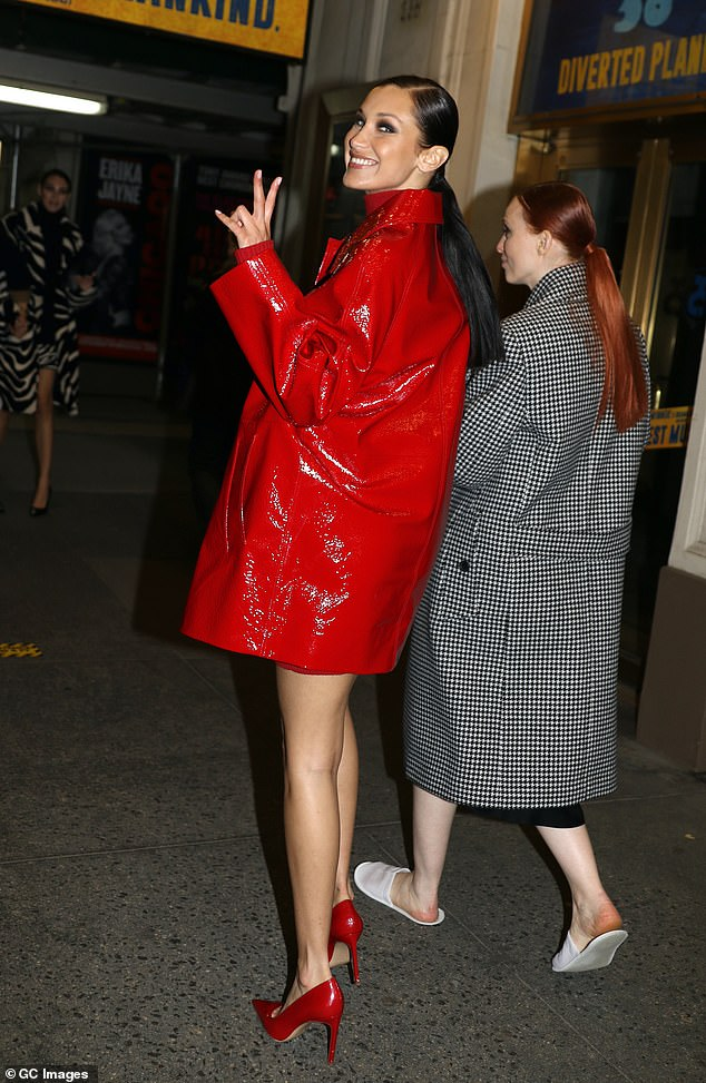 Sign: The statuesque stunner flashed a peace sign at photographers as she entered the theatre