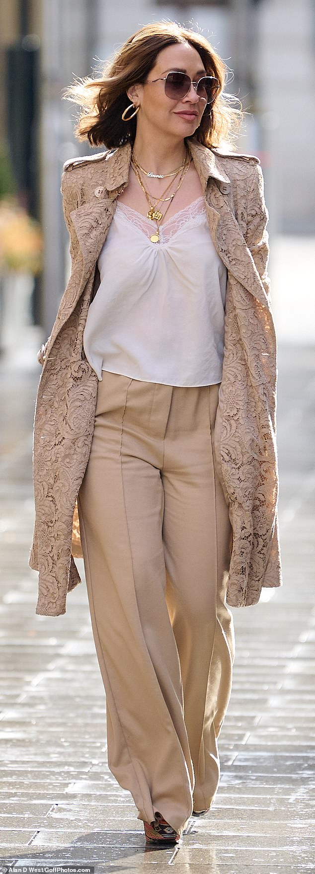 Strutting her stuff:She appeared in great spirits as she teamed her nude outerwear with some sophisticated wide-legged beige trousers