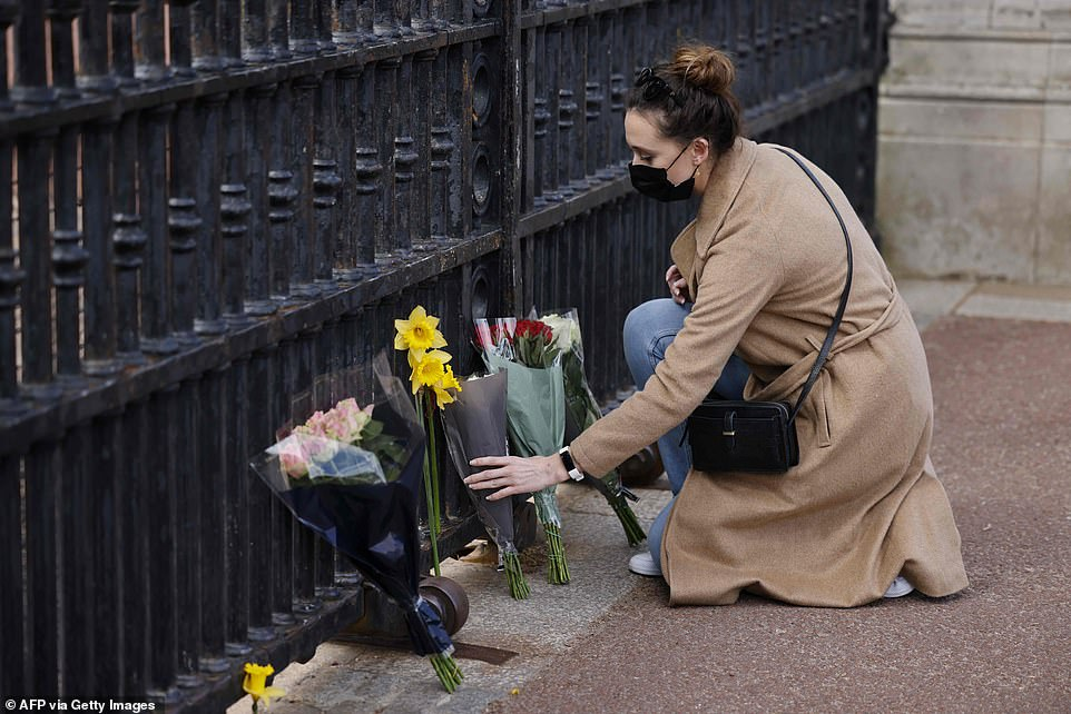 A woman lays a bunch of flowers at the gates of Buckingham Palace in central London on Friday afternoon after the announcement of the death of Philip