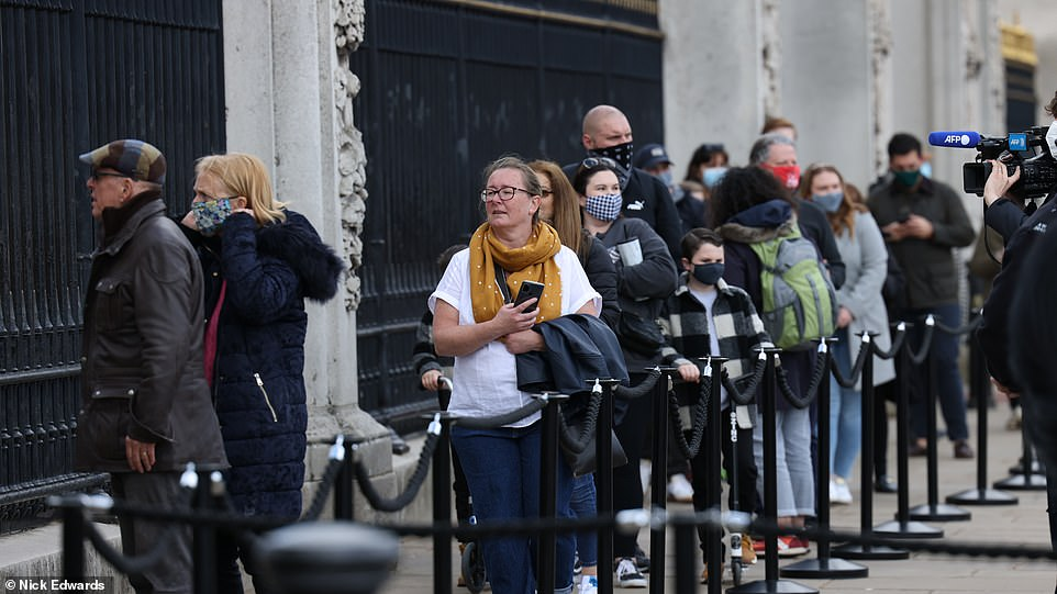 People queue to take pictures and look at a sign hanging on Buckingham Palace after the news Prince Philip had died