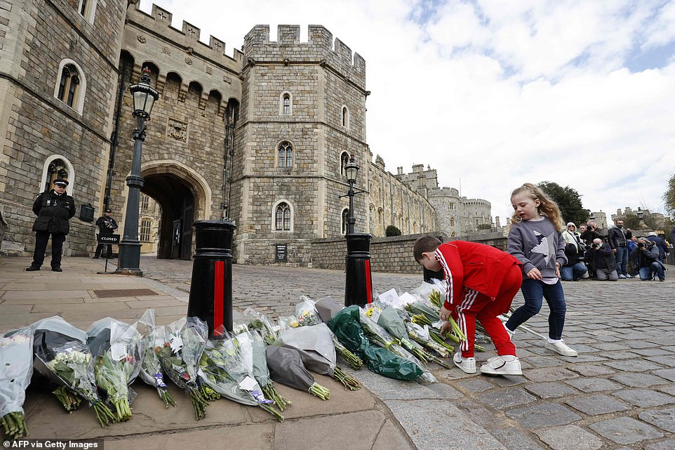 Children add to the floral tributes outside the Henry VIII Gate of Windsor Castle, in Windsor, west of London