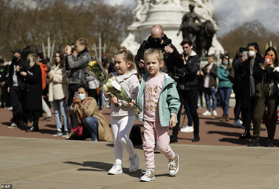 Two young girls prepare to leave flowers in front of the gate at Buckingham Palace in London, after the announcement