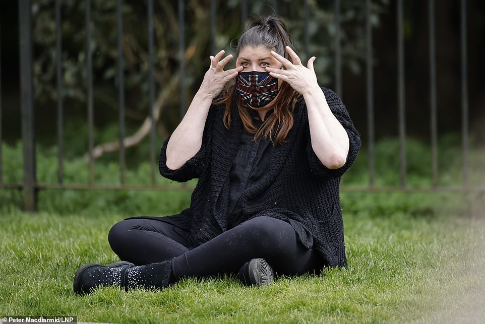 A woman wearing a Union flag face covering wipes away tears as she sits outside Windsor Castle on The Long Walk in Berkshire