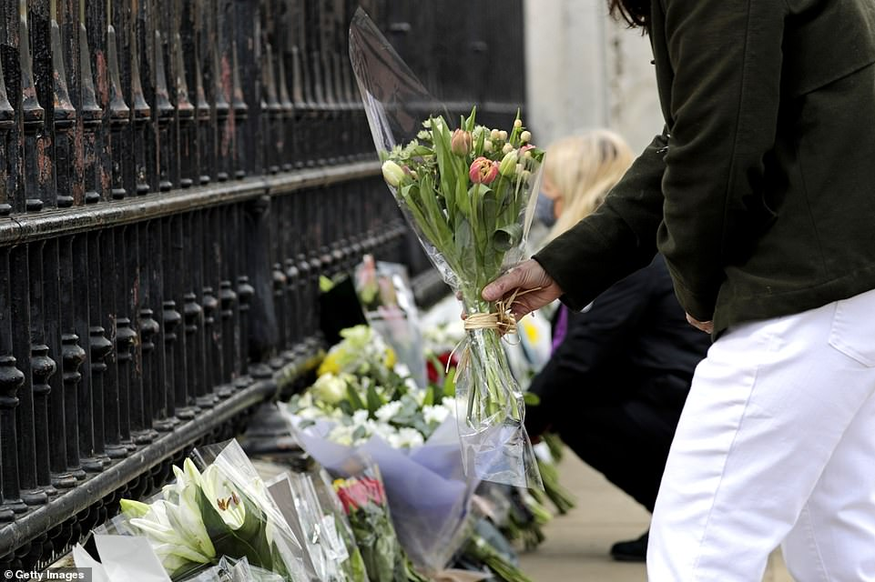 Members of the public lay floral tributes outside Buckingham Palace on Friday afternoon as they wish their best to the Queen