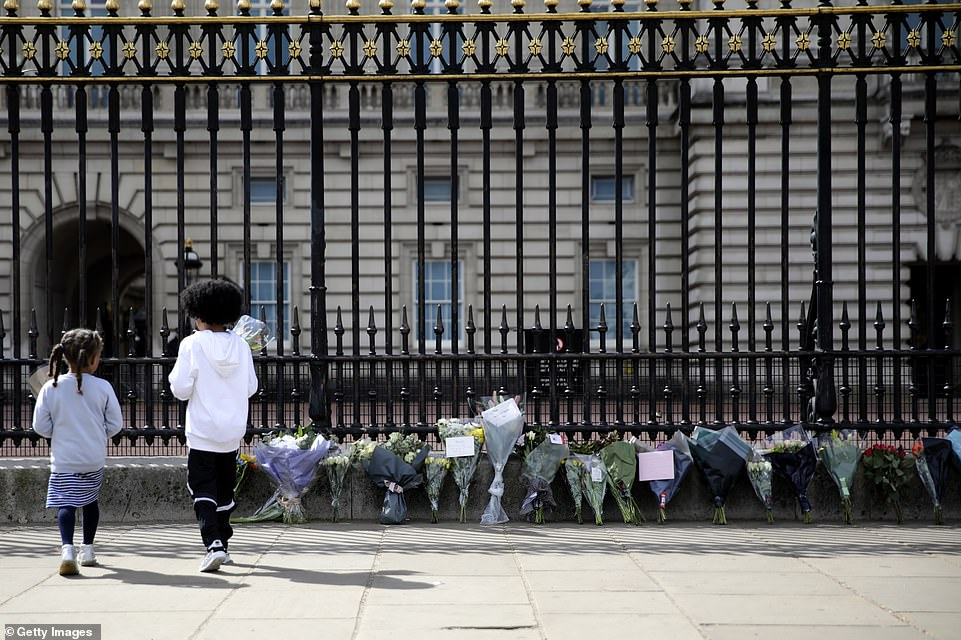 Children lay floral tributes outside Buckingham Palace in central London