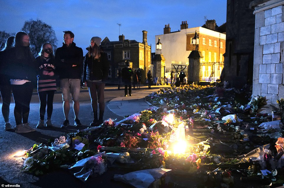 Mourners look on as flowers are leftat the gates of Windsor Castle at the top of the long walk