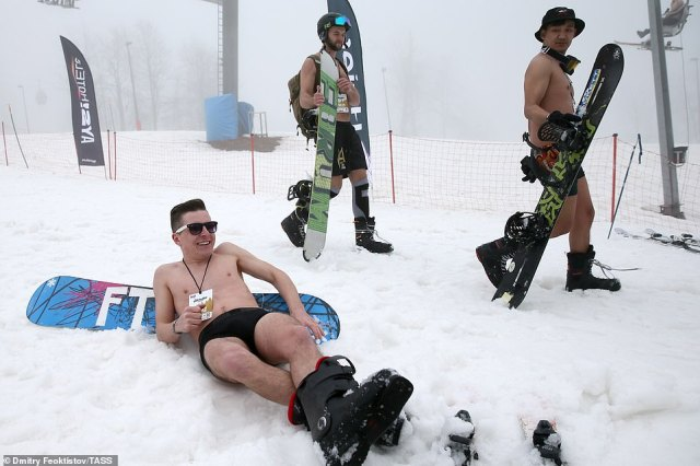 Chilling out! One reveller lounged on the freezing ground and lay against his snowboard while enjoying the festival