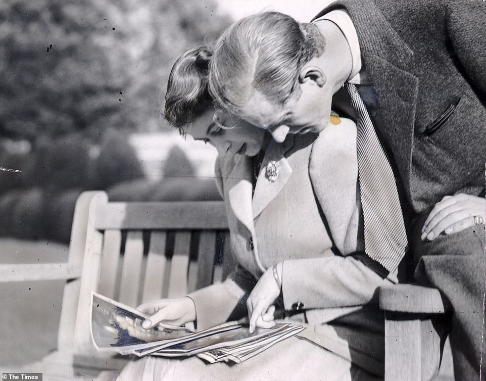 Princess Elizabeth and the Duke of Edinburgh, on honeymoon, photographed in the grounds of Broadlands looking at their wedding photographs, on November 23, 1947