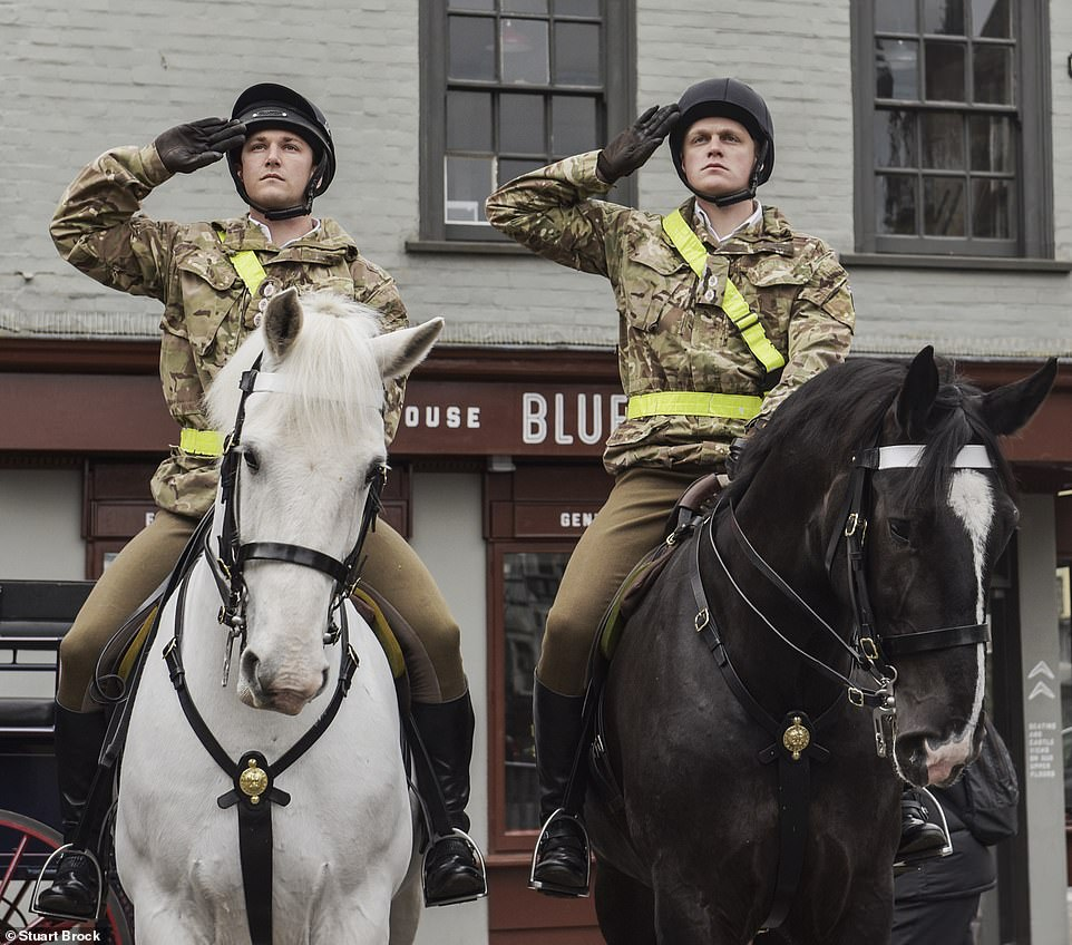 Soldiers from a mounted regiment salute as they pass Windsor Castle, where Philip will rest until his funeral in a week's time
