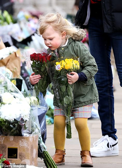 Little girls left floral tributes to the Duke outside Buckingham Palace this afternoon