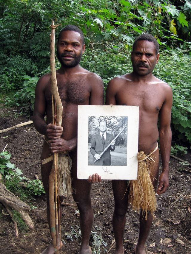 Two warriors from the Yaohnanen tribe of the Pacific Island of Tanna, in Vanuatu, holding a picture of Prince Philip with a war club which was sent to him from their village