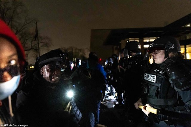 Protestors face off with a line of police officers in front of the Brooklyn Center Police Station