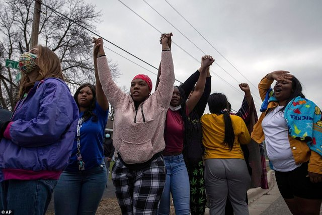 People raise their arms in protest, Sunday, April 11, 2021, in Brooklyn Center