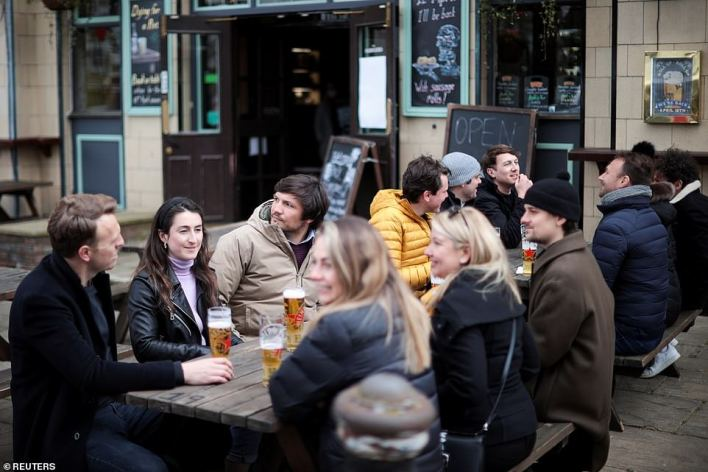 People enjoy their drinks at the Georgian Arms pub in London following its reopening today, although venues with no outside space have had to remain shut
