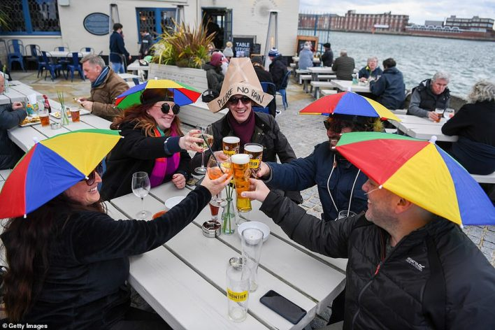 Revellers wearing umbrellas on their heads enjoy a drink outside at The Still & West pub at Spice Island in Portsmouth