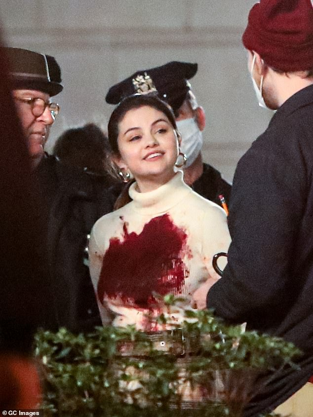 Action: Cameras rolled as Selena was handcuffed and driven to a waiting vehicle as her ivory turtleneck was stained with dried blood as she walked with her hands cuffed behind her back