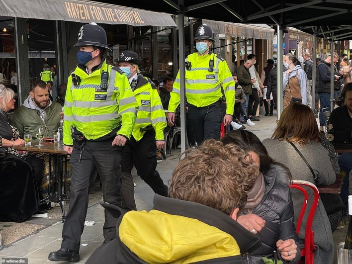 Police were out in force in Soho earlier today as drinkers rushed to outdoor areas to enjoy their first pint since lockdown began in January