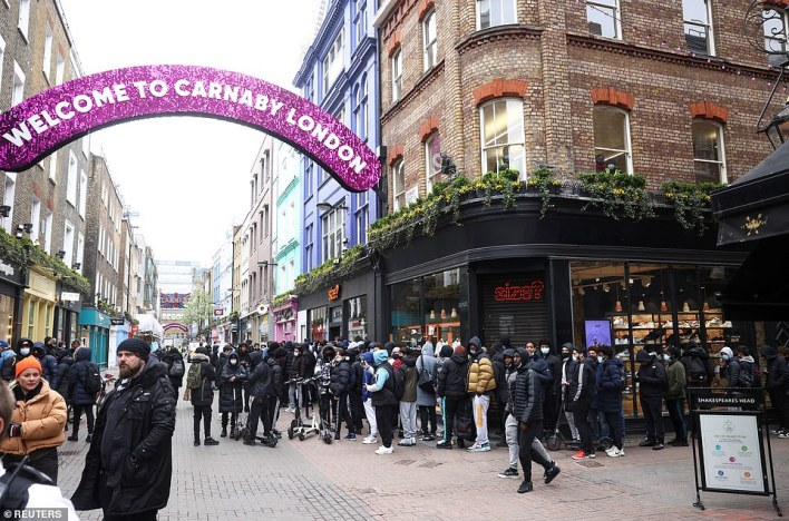 Large crowds queue outside a shop selling clothes and trainers early this morning on Carnaby Street
