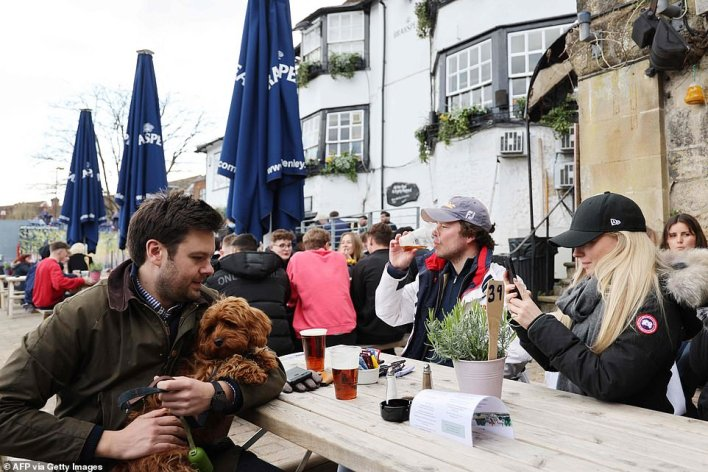 A customer brings their dog along to enjoy a drink outside The Angel on the Bridge pub in Henley on Thames