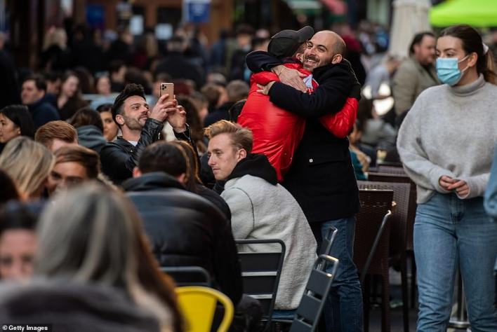 Two men embrace amongst people drinking outside in Soho as non essential retail and pubs reopened today for the first time in four months