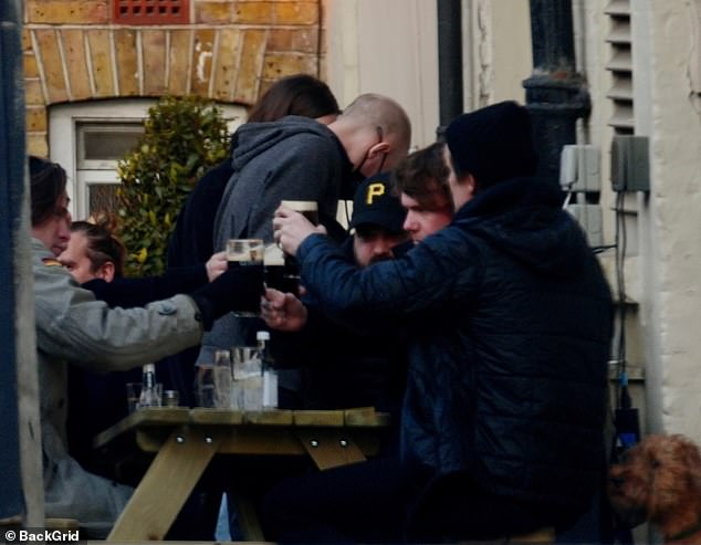 Cheers!The Crown actor, 38, joined pals on a bench outside a pub in London, raising a pint of Guinness to toast the occasion