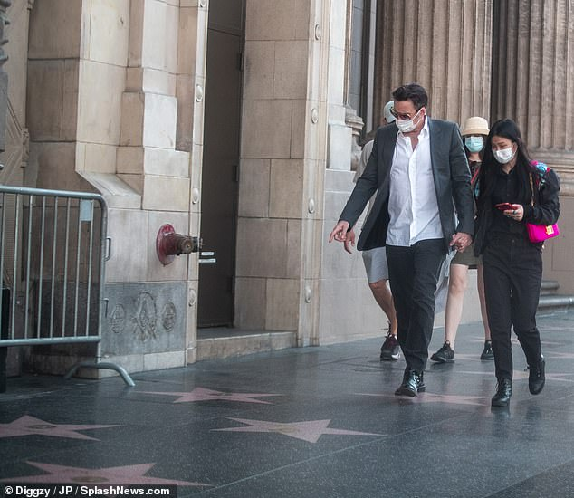 Movie star status:The National Treasure star wore dress shoes with a face mask and sunglasses