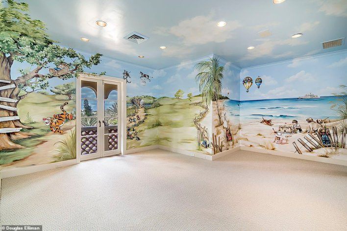 Children will love the creative look and fun murals of the beach painted on the walls of this playroom
