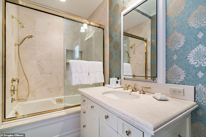 This blue and gold furnished bathroom is elegantly appointed complete with gold taps and a golden shower