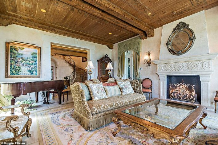 A lounge area downstairs looks like a scene from a stately home complete with grand piano and fireplace