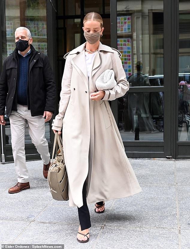 De moda: Debajo de su abrigo, llevaba una camiseta blanca lisa y pantalones largos negros, completando el atuendo sutil con sandalias negras de tiras.