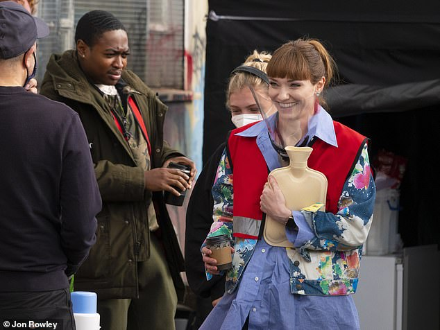 She's pleased:Clutching a takeaway coffee and a hot water bottle, the actress appeared to be in high spirits as she relaxed on set with her co-stars