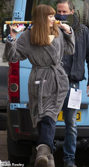 Optimista: luciendo cómodos jeans y botas Ugg, la actriz se mantuvo entretenida durante un momento tranquilo en el set.