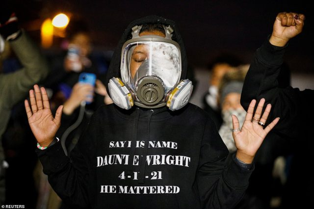 A protester in a gas maskgestures as activists confront State troopers, National Guard members and other law enforcement officersfollowing a march for Daunte Wright on Tuesday