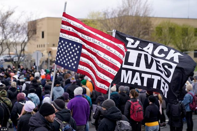 A demonstrator carries a flag bearing the names of people of color killed by police at a rally outside the Brooklyn Center Police Department to protest the shooting death of Daunte Wright