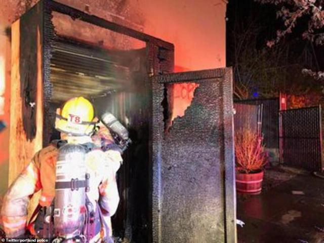 Firefighters arrive on the scene after protesters set fire to Portland police union building
