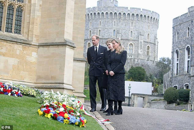 The Earl of Wessex, Lady Louise Windsor and the Countess of Wessex view flowers outside St George's Chapel today