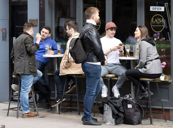 Revellers in London's Soho drinking in the afternoon sun on the first Friday since pubs were allowed to reopen outdoors