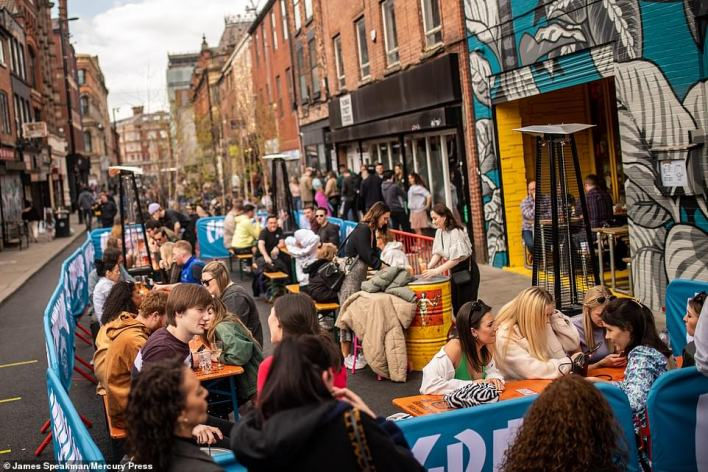 People in Manchester enjoy the warm weather as they sit outside bars and restaurants on Thomas Street this afternoon