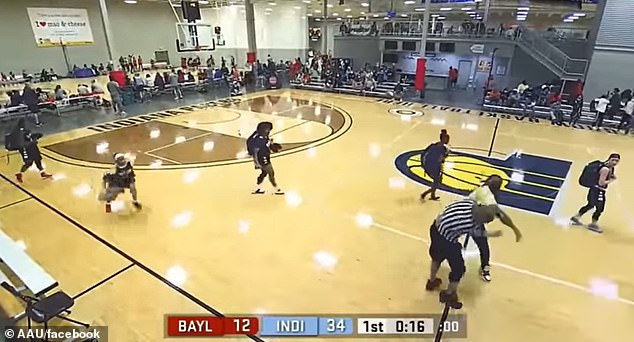 The spectator in the yellow shirt punches the referee, at which point a player from Baylor Basketball drops her bag and runs over