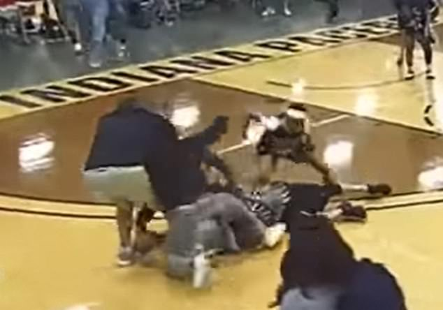 The Baylor player proceeds to punch the referee while he lays on the floor